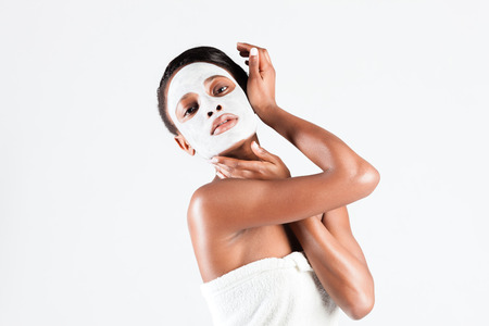 african mask: Young African woman in Studio doing body care with refreshing facial mask for young and beautiful skin and relaxation
