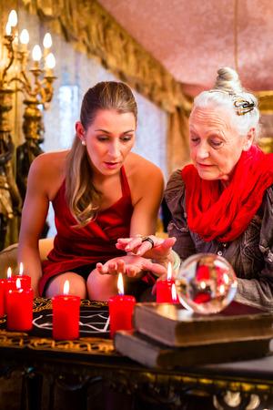 adivino: Mujer adivino o esot�rica Oracle, ve en el futuro mediante la lectura de manos durante una sesi�n de espiritismo para interpretarlos y para responder a las preguntas Foto de archivo