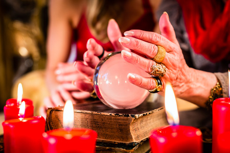 soothsayer: Female Fortuneteller or esoteric Oracle, sees in the future by looking into their crystal ball during a Seance to interpret them and to answer questions Stock Photo