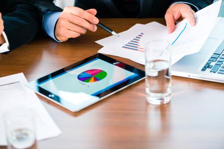 비지니스 - 은행, 관리자 또는 전문가는 태블릿 컴퓨터에 수치를 평가하여 실시간으로 개발 사업의 비교