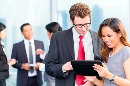 Portrait of Asian business people looking at tablet together photo