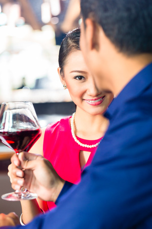 Portrait of young Asian couple toasting with wine photo