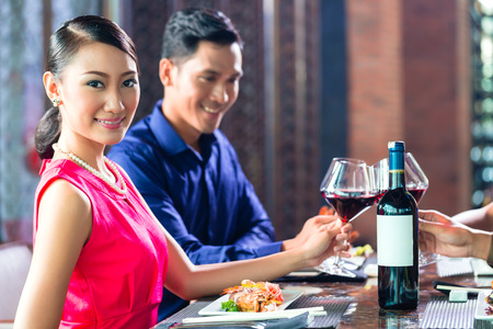 Asian Friends celebrating with red wine in restaurant photo