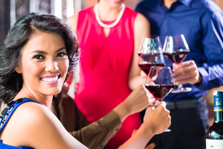 Asian Friends toasting with red wine in restaurant photo