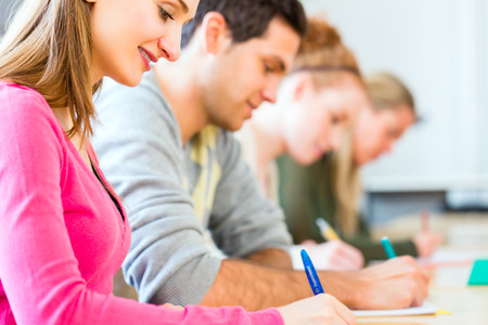 examination stress: University college students writing test or exam Stock Photo