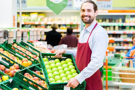 oficinista: Secretario Supermercado llenando bastidores de almacenamiento de manzana en el departamento de la fruta Foto de archivo