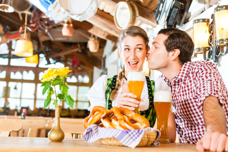 Bavarian couple wearing traditional dress, flirting and  drinking beer in restaurant photo