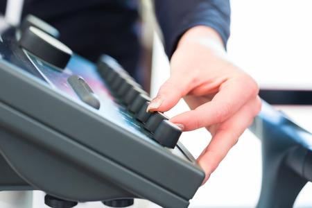Weibliche Trainer Regulierung Intensität der ems Elektromuskelstimulation Maschine Standard-Bild