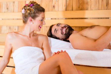 Couple sitting in wellness spa sauna photo