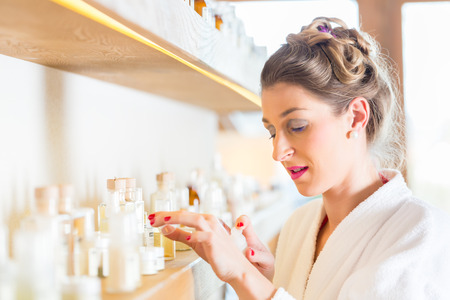 bath gown: Woman in bath robe choosing face care products in wellness spa  Stock Photo