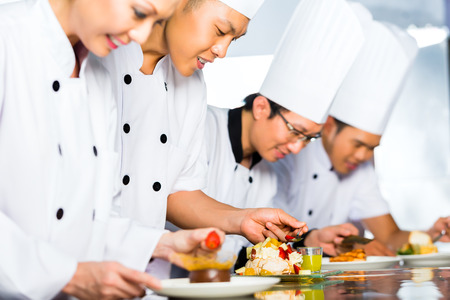 asian chef: Asian Indonesian chef along with other cooks in restaurant or hotel kitchen cooking, finishing dish or plate for dessert Stock Photo