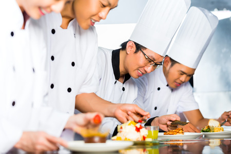 Asian Indonesian chef along with other cooks in restaurant or hotel kitchen cooking, finishing dish or plate for dessert photo
