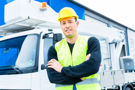 builder or driver standing in front of pallet transporter or lift fork truck on construction or building site
