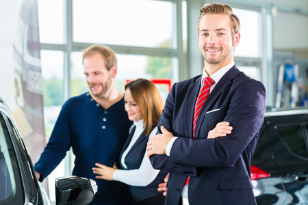 Seller or car salesman and clients or customers in car dealership presenting the interior decoration of new and used cars in the showroom Stock Photo
