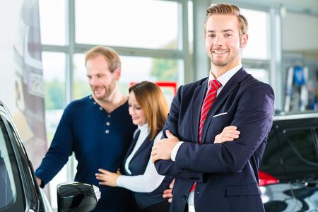 Vendeur ou vendeur de voiture et les clients ou les clients en concession automobile présentant la décoration intérieure des voitures neuves et d'occasion dans la salle d'exposition