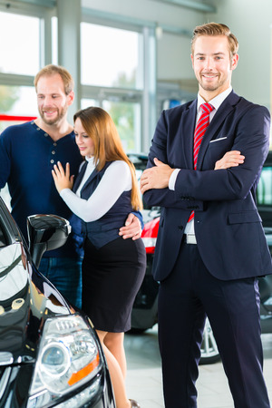 Seller or car salesman and clients or customers in car dealership presenting the interior decoration of new and used cars in the showroom photo
