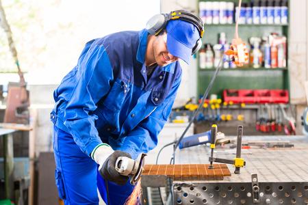 Craftsman sawing metal with disk grinder in workshop photo