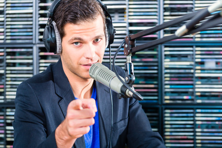 matiging: Man Presenter in radiostation hosting-show voor radio wonen in Studio Stockfoto