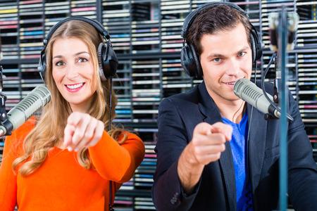 Los presentadores y moderadores - hombre y mujer - en la estación de radio espectáculo de alojamiento para la radio en directo en el estudio Foto de archivo