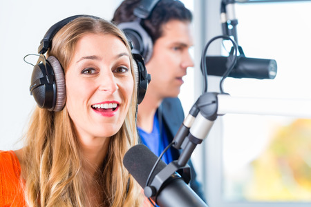 work station: Presenters or moderators - man and woman - in radio station hosting show for radio live in Studio