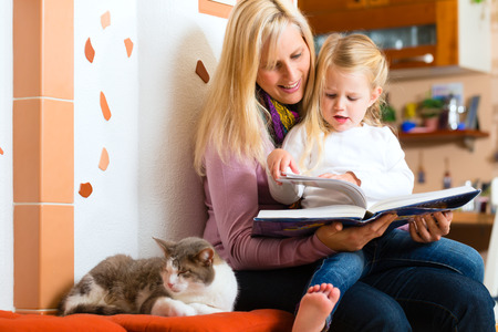 woman night: Mother reading tired daughter good night story out of storytelling book