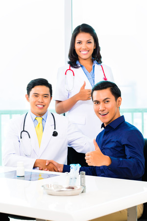 Asian doctor giving patient handshake for complete healing in practice or surgery