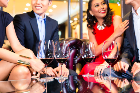 friends drinking: Asian friends chatting and drinking red wine Stock Photo