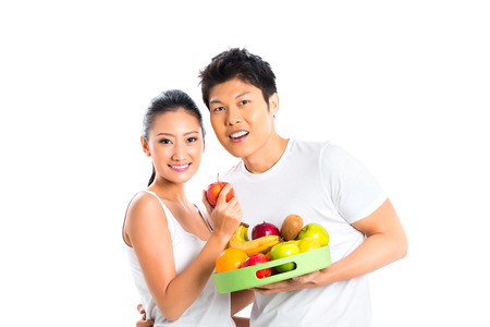 Young Asian couple eating fruits and having fun  photo