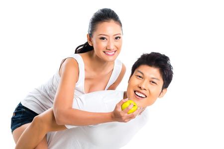 Young Asian man wearing woman piggyback, eating fruits and having fun  photo