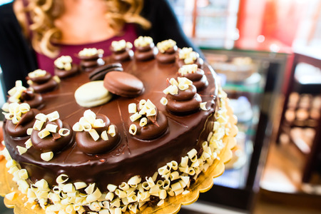pastry shop: Female confectioner presenting tray of cake in bakery or pastry shop