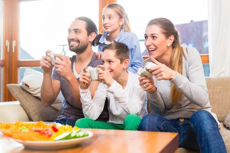 niños jugando videojuegos: Familia tener tiempo libre juntos y jugando con la consola de videojuegos