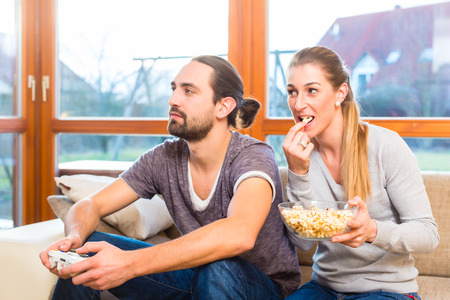 snack time: Couple having leisure time together and playing with video game console