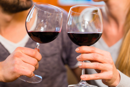 Young handsome couple drinking red wine at home Stock Photo