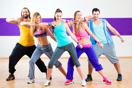 Grupo de hombres y mujeres bailando Zumba Fitness coreografía en la escuela de baile