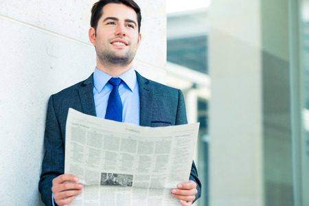 Handsome businessman or manager, in front of modern office architecture, reading newspaper photo