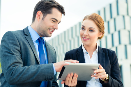 Business people or businessman and businesswoman working outdoor, using pad or tablet computer photo