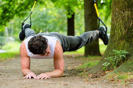 man exercising with suspension trainer sling in City Park under summer trees for sport fitness photo
