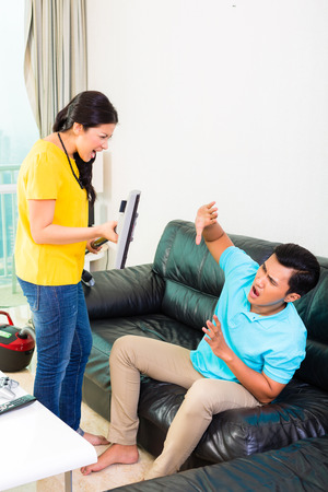 household tasks: Young Asian handsome couple having relationship difficulties with household tasks like vacuum and playing games on couch Stock Photo