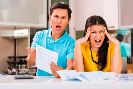 Jeune couple beau combat et cris asiatique en raison de département financier et factures impayées dues