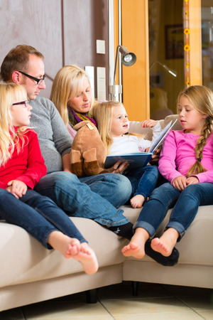 Family sitting together with mother, father and children comfortable on sofa, listening to fairy tale from story book photo