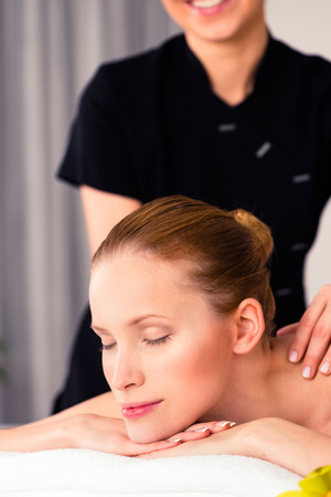 Massager giving woman in wellness beauty spa back massage with essential oil