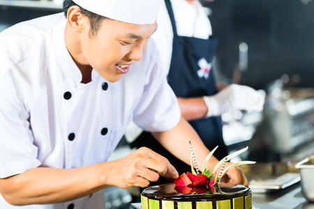 Close up of young chef decorating cake photo