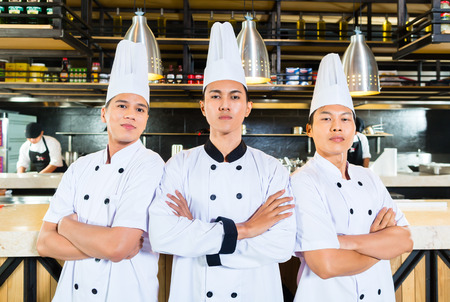 Young chefs standing with arms crossed photo