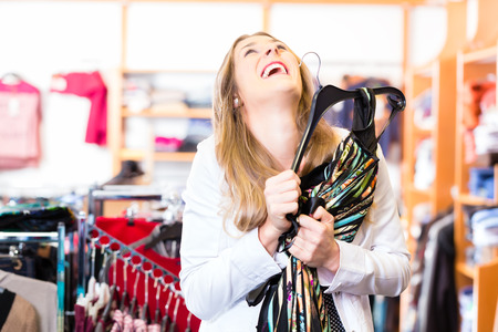 bargain: Woman shopping in boutique or fashion store choosing clothes on a hanger Stock Photo