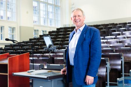 Profesor de la universidad dando clase y de pie en el escritorio