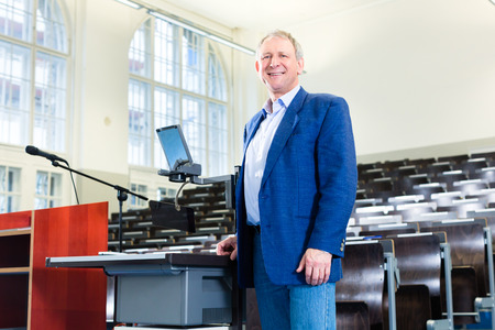 college professor: College professor giving lecture and standing at desk