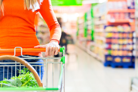 super market: Woman driving shopping cart while grocery shopping in supermarket