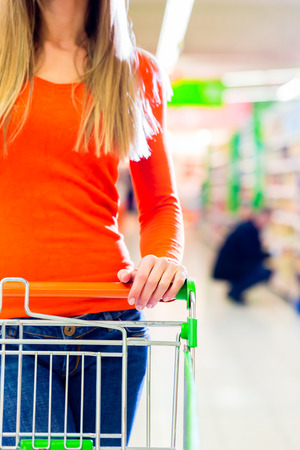 Woman driving shopping cart while grocery shopping in supermarket  photo