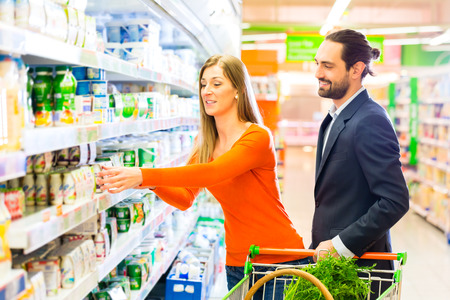Couple selecting dairy products while grocery shopping in supermarket  photo