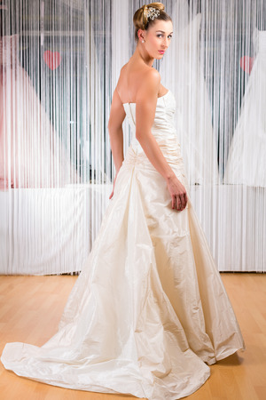 Woman trying on wedding dress or bridal gown in wedding fashion store photo
